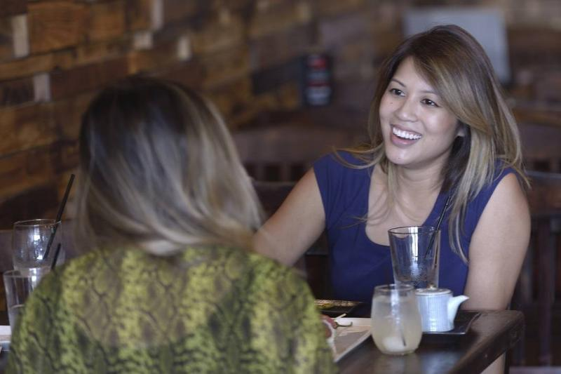 Two women laugh while eating dinner out.