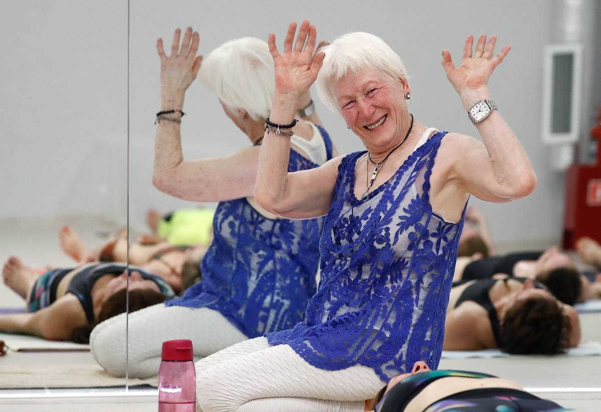 A 79-year-old yoga teacher waves to the camera during a class.