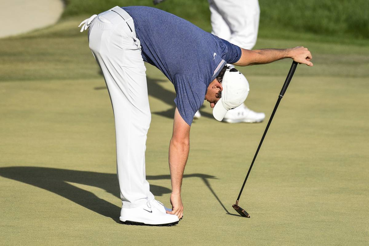Rory McIlroy bends over to pick up a golf ball.