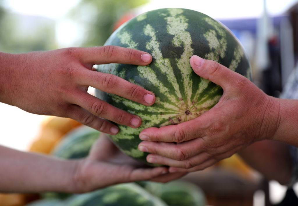 Someone hands a watermelon to another.