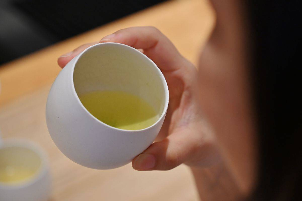 A woman looks at a glass of green tea.