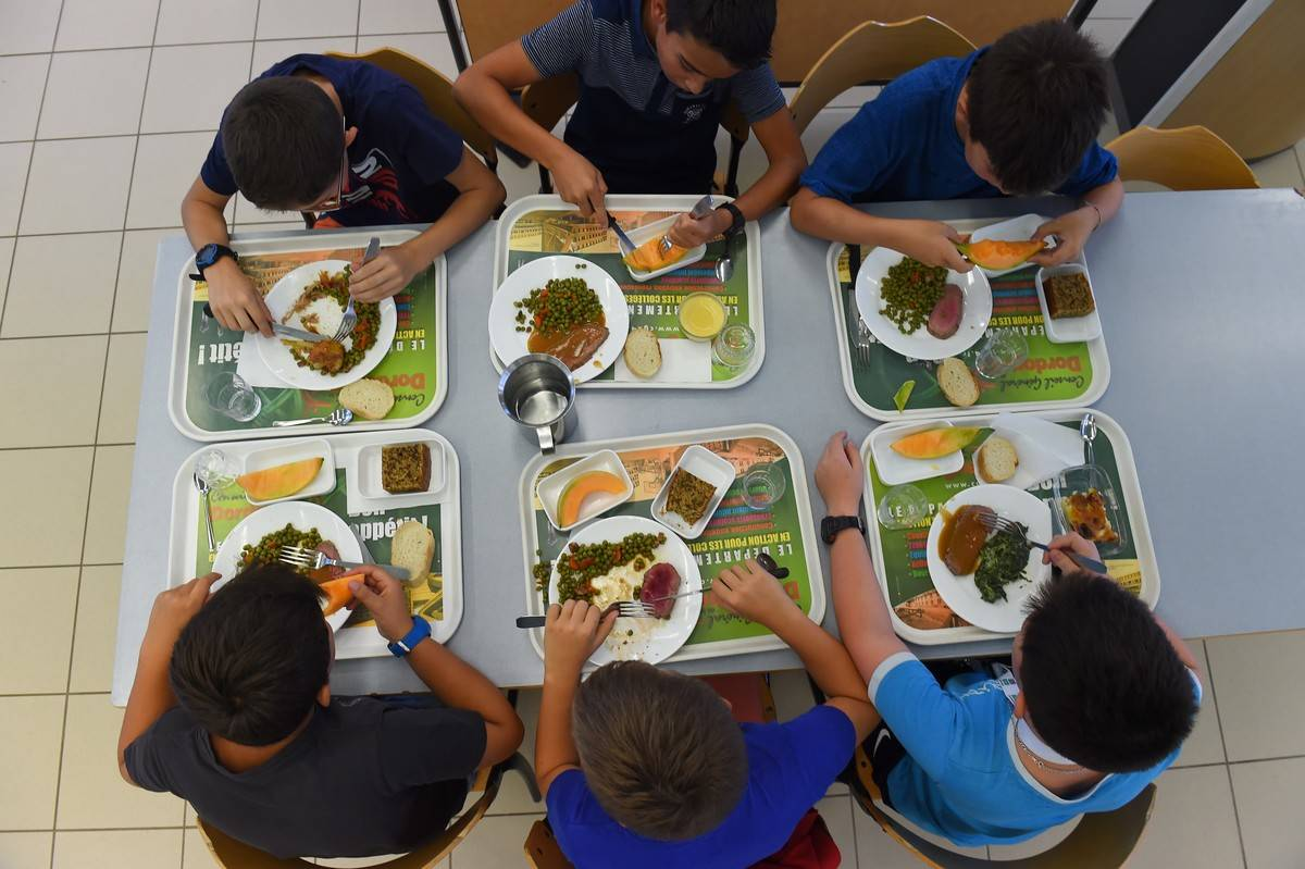 Students eat lunch from cafeteria trays.