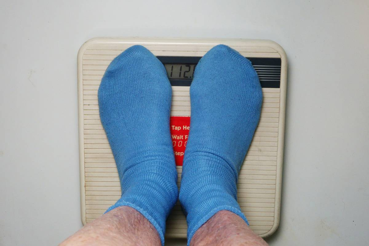A person weighs himself on a scale.