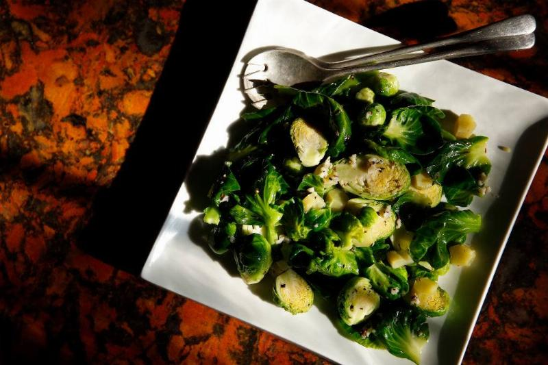 A plate of brussel sprouts sits on a table.