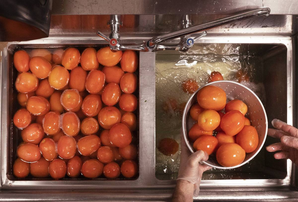 A person washes tomatoes in a colander in the sink.