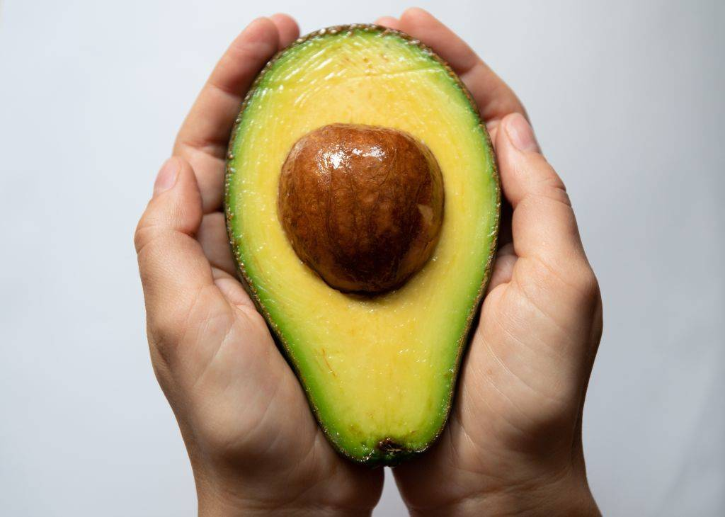 A person holds a cut open avocado in their hands.