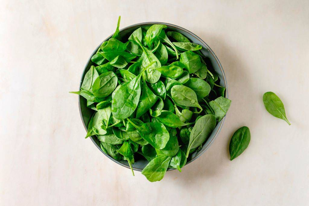 A bowl of baby spinach sits on a white counter.