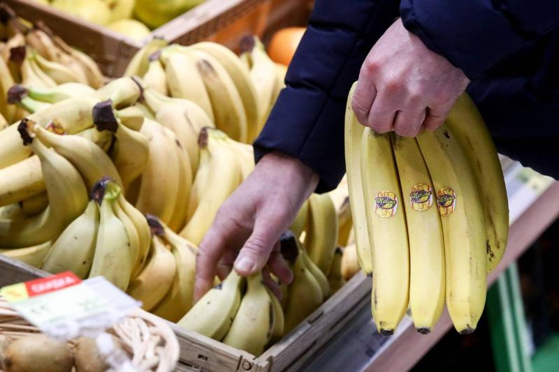A man shops for bundles of bananas at a supermarket.