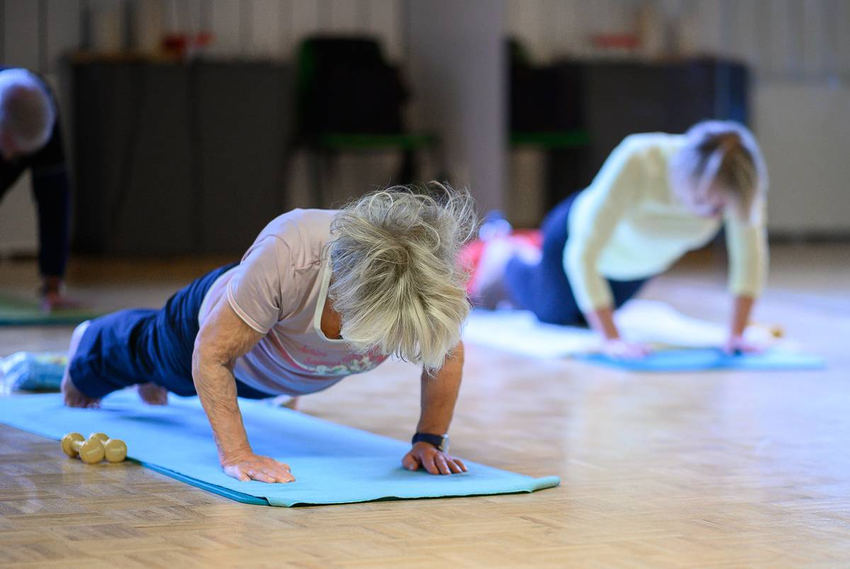 Older women do push-ups during an exercise lesson for people over 60.