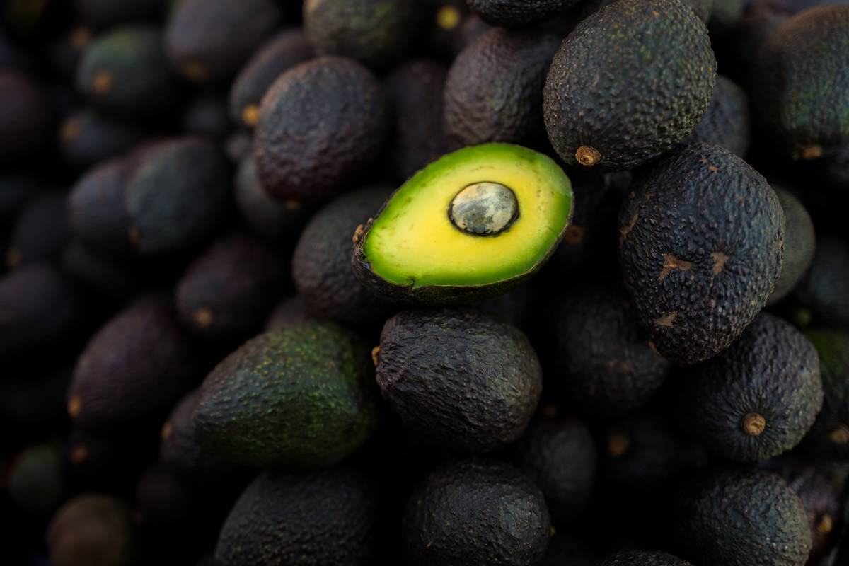 Ripe avocados sit in a pile.