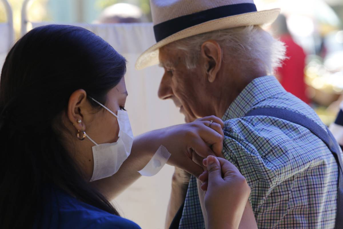 A woman vaccinates an older man against influenza.