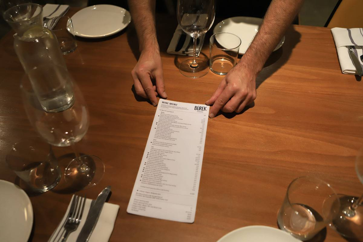 A person holds out a restaurant menu.