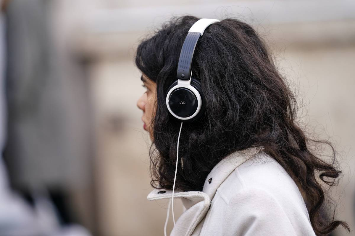 A woman listens to music using headphones.