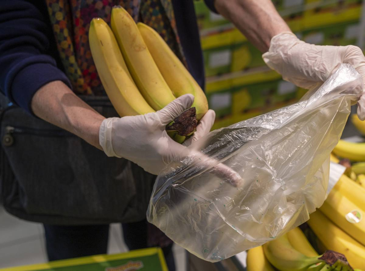 An employee bags bananas.