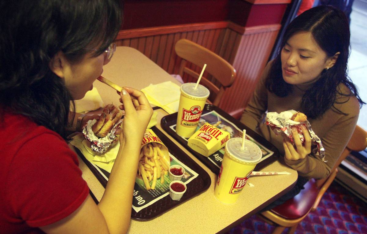 Two women eat fries and burgers at Wendy's.