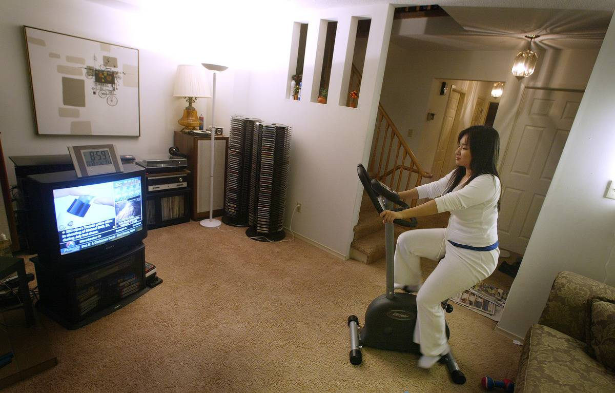 A woman works out on her exercise bike while watching TV.
