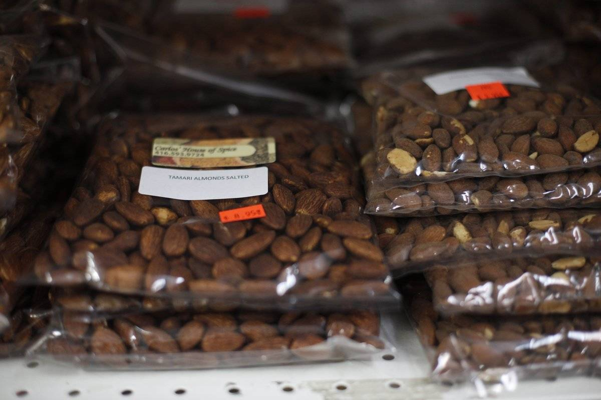 Packaged almonds sit on a shelf in a supermarket.