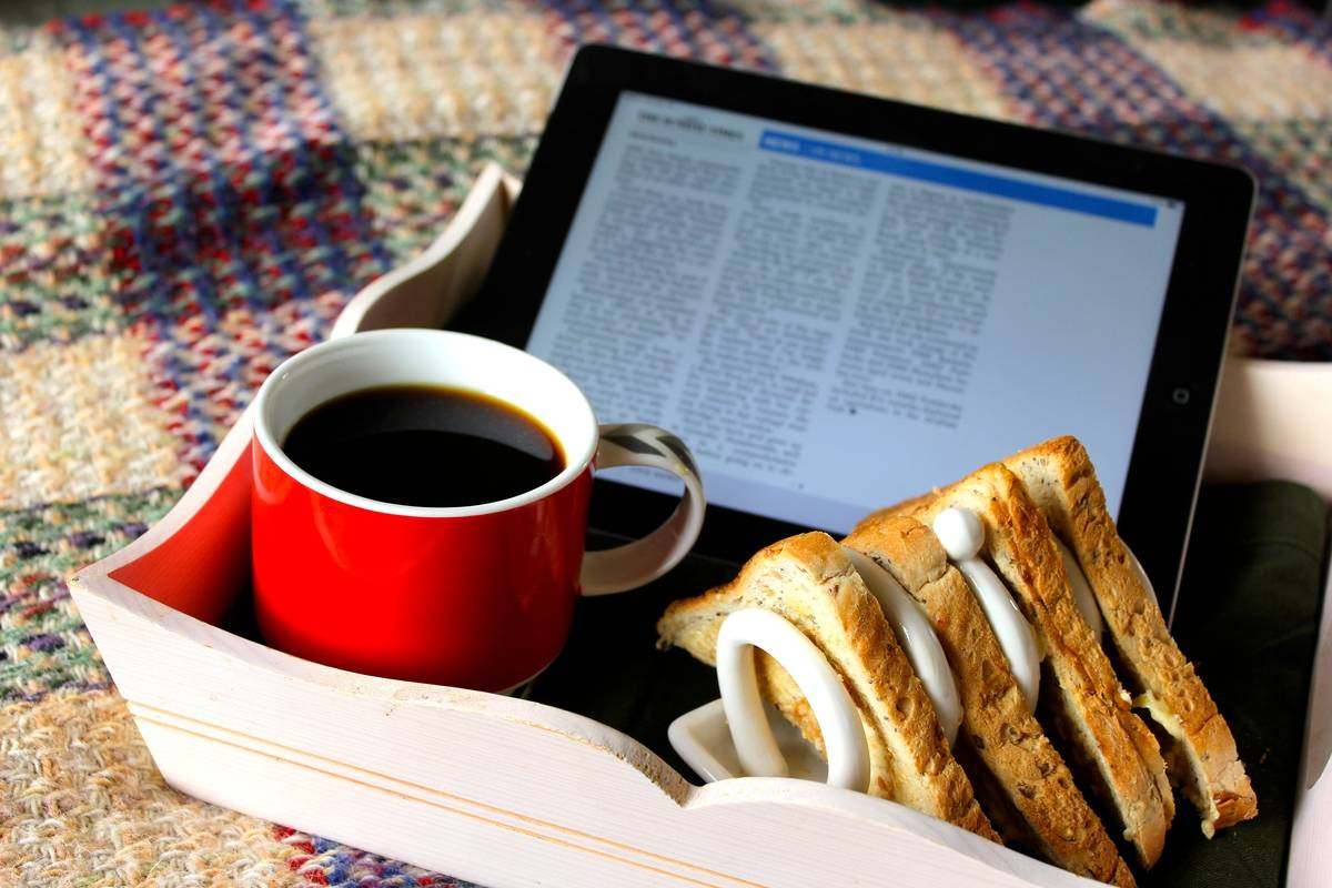 A breakfast tray features coffee, a sandwich, and the newspaper on an iPad.