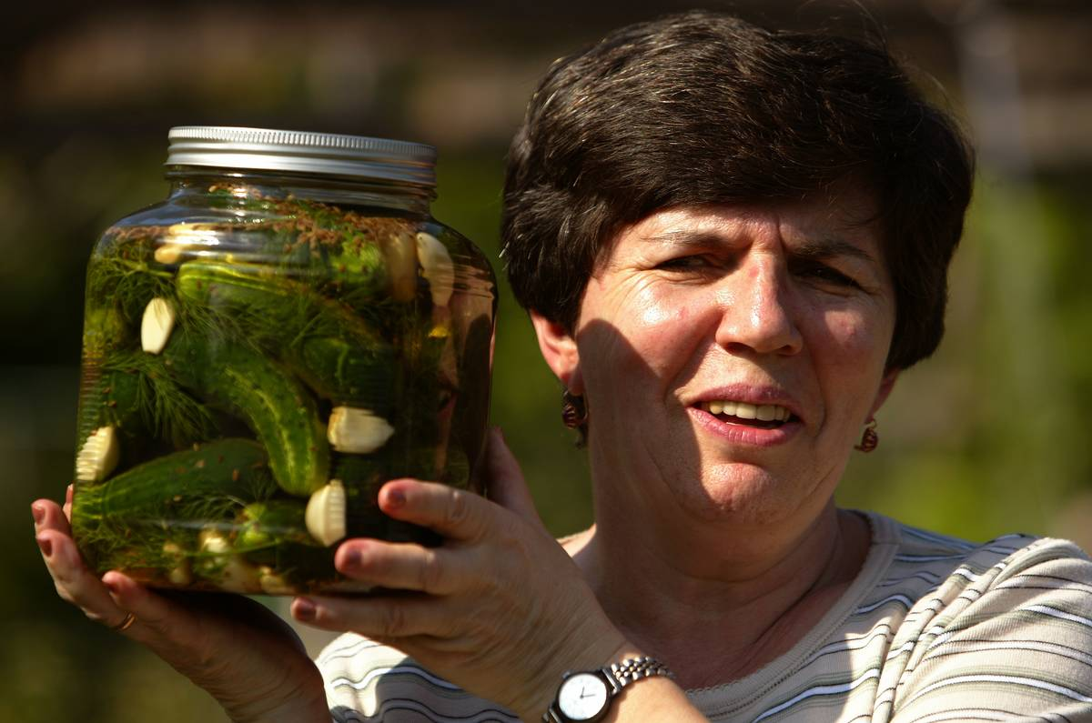 A woman holds up a jar of dill pickles.