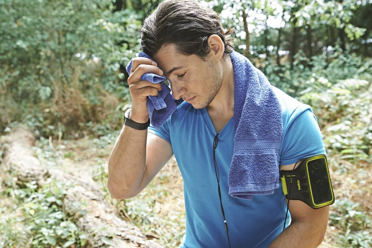 A man wipes sweat off his forehead while running on a fitness trail.