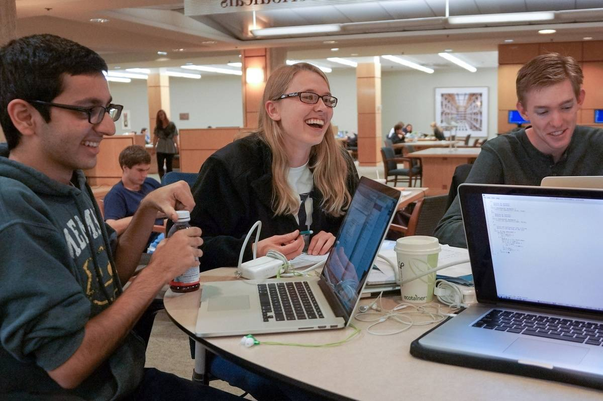 Three students study together in a library.