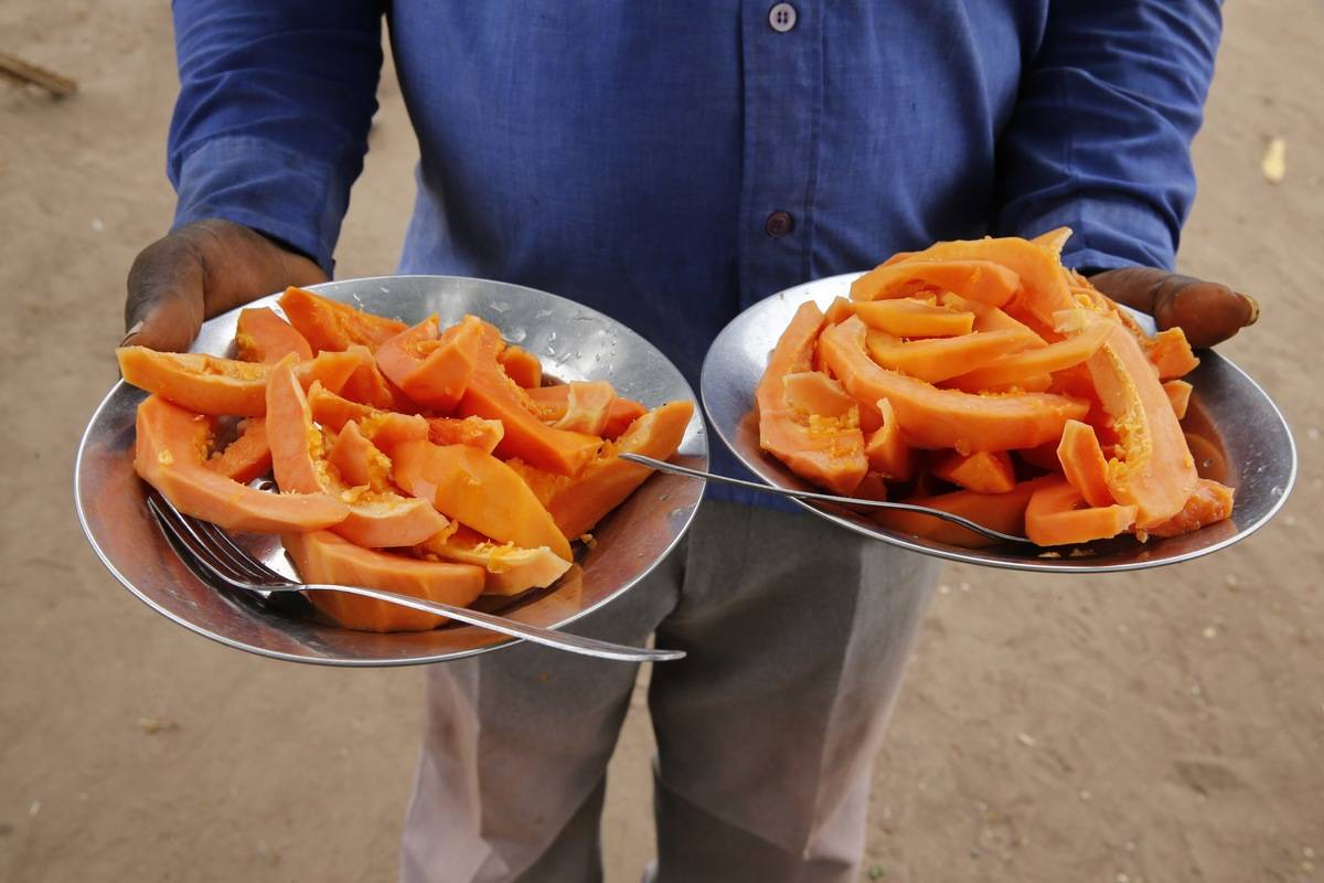 A man holds two plates of sliced papaya.