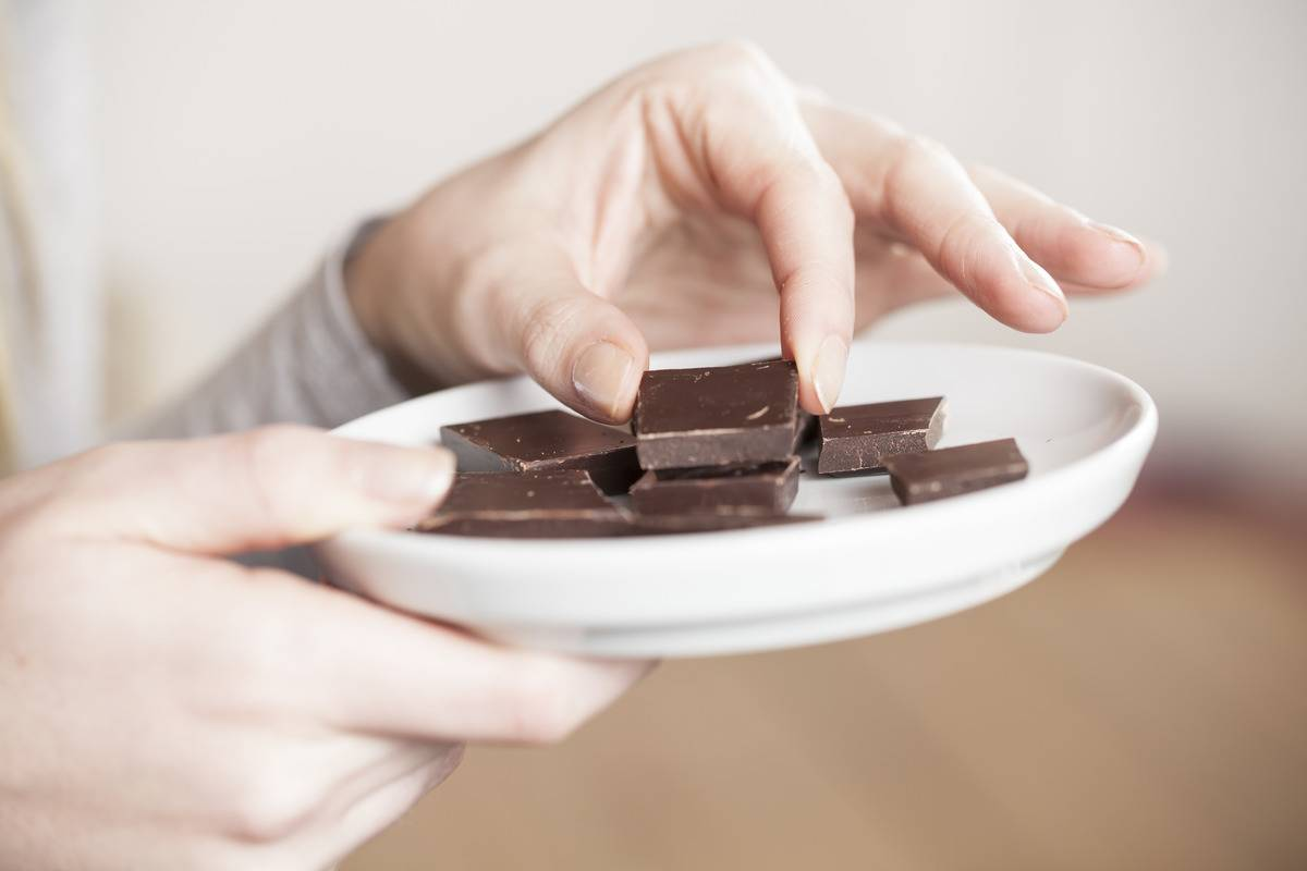 A woman eats squares of chocolate off of a plate.