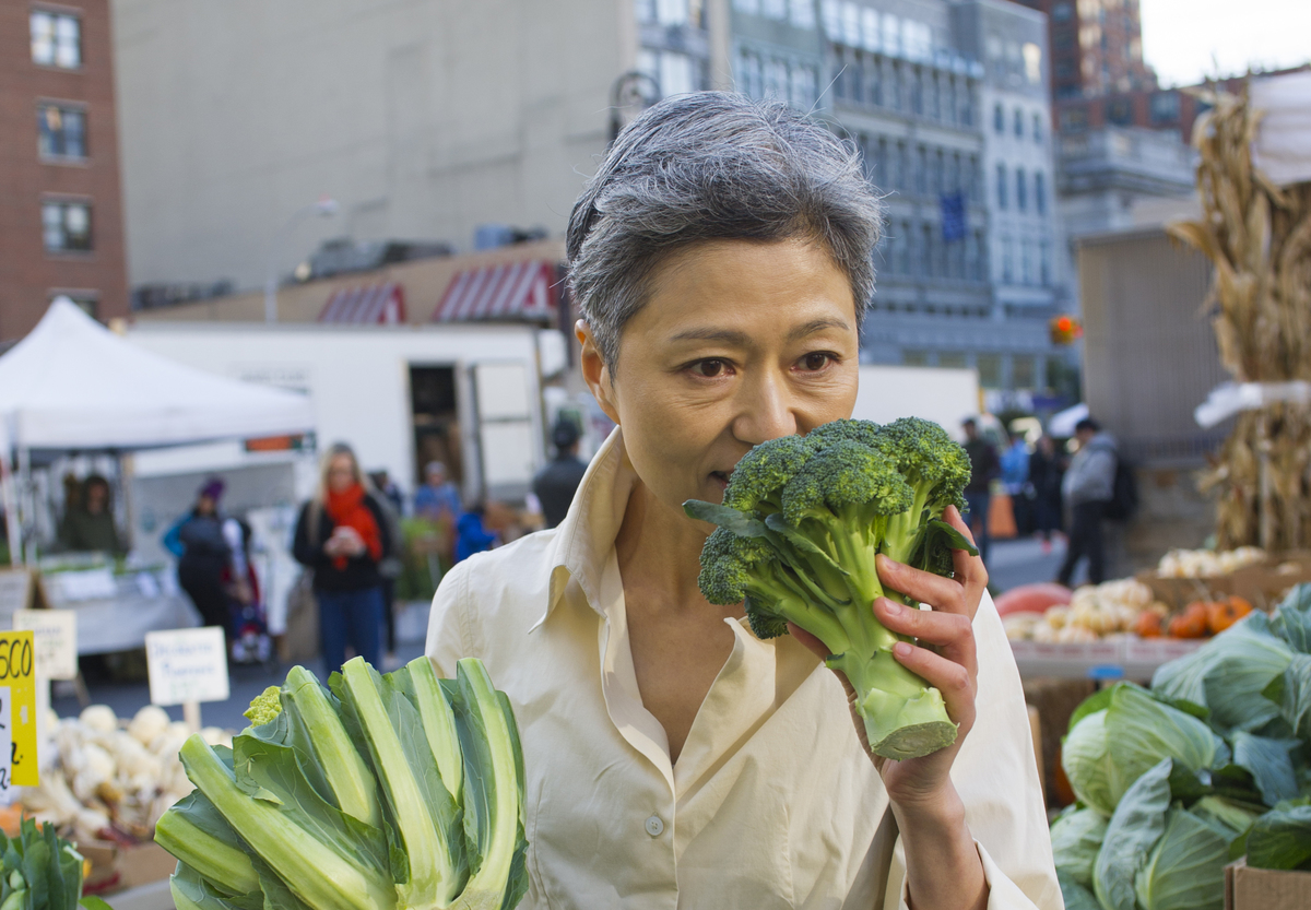 A woman smells fresh broccoli at a farmer's market.