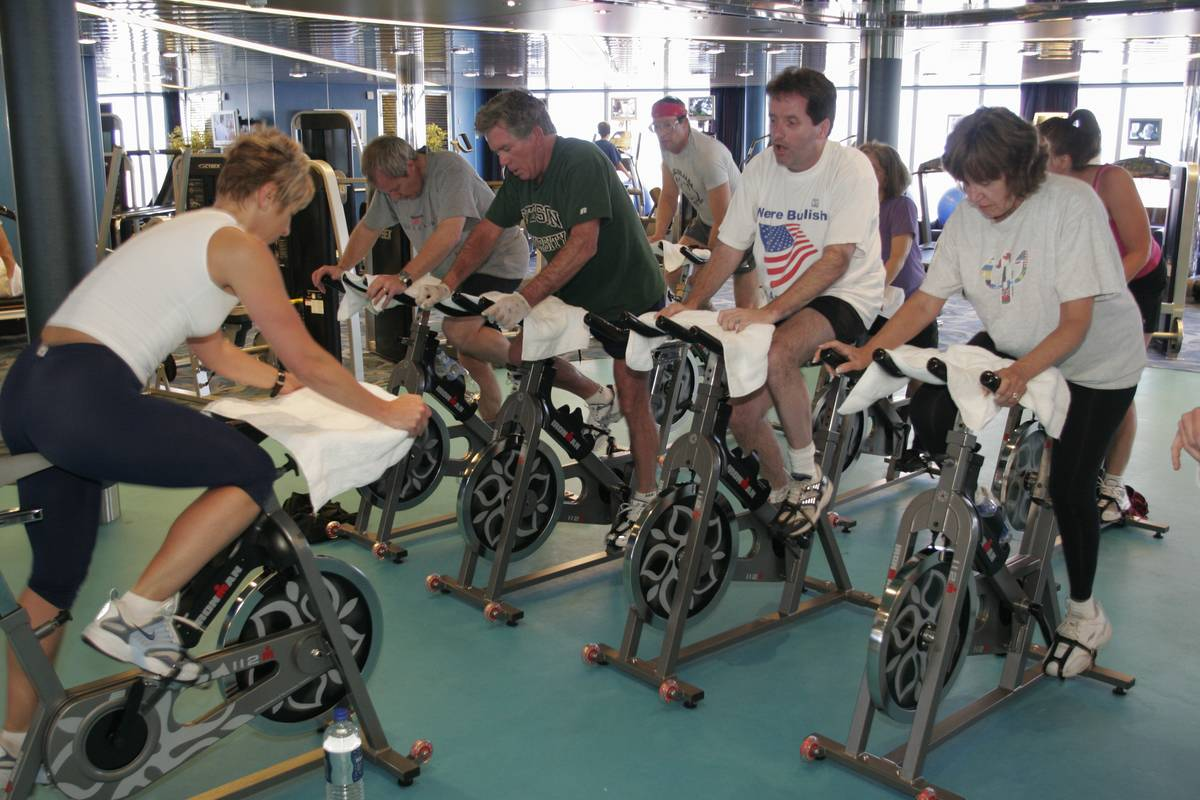 People ride exercise bikes during a workout class.
