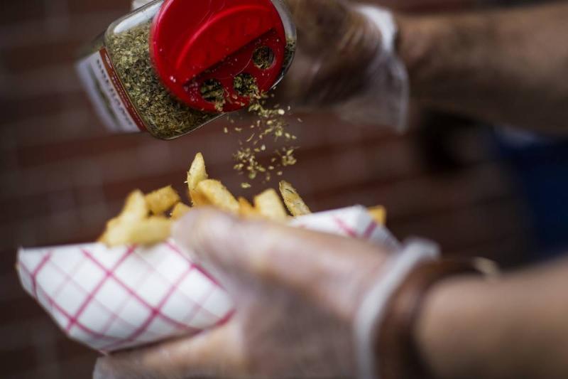 A chef sprinkles oregano on Greek fries.