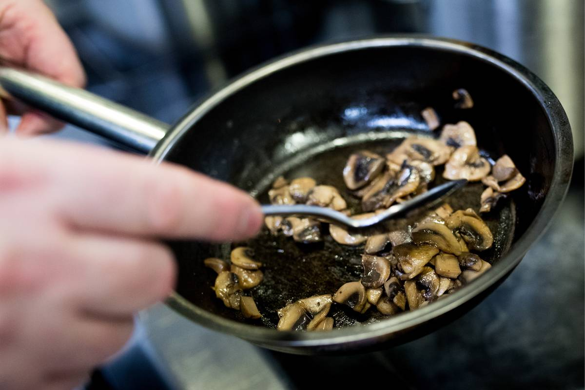 A chef sautees sliced mushrooms in a pan.