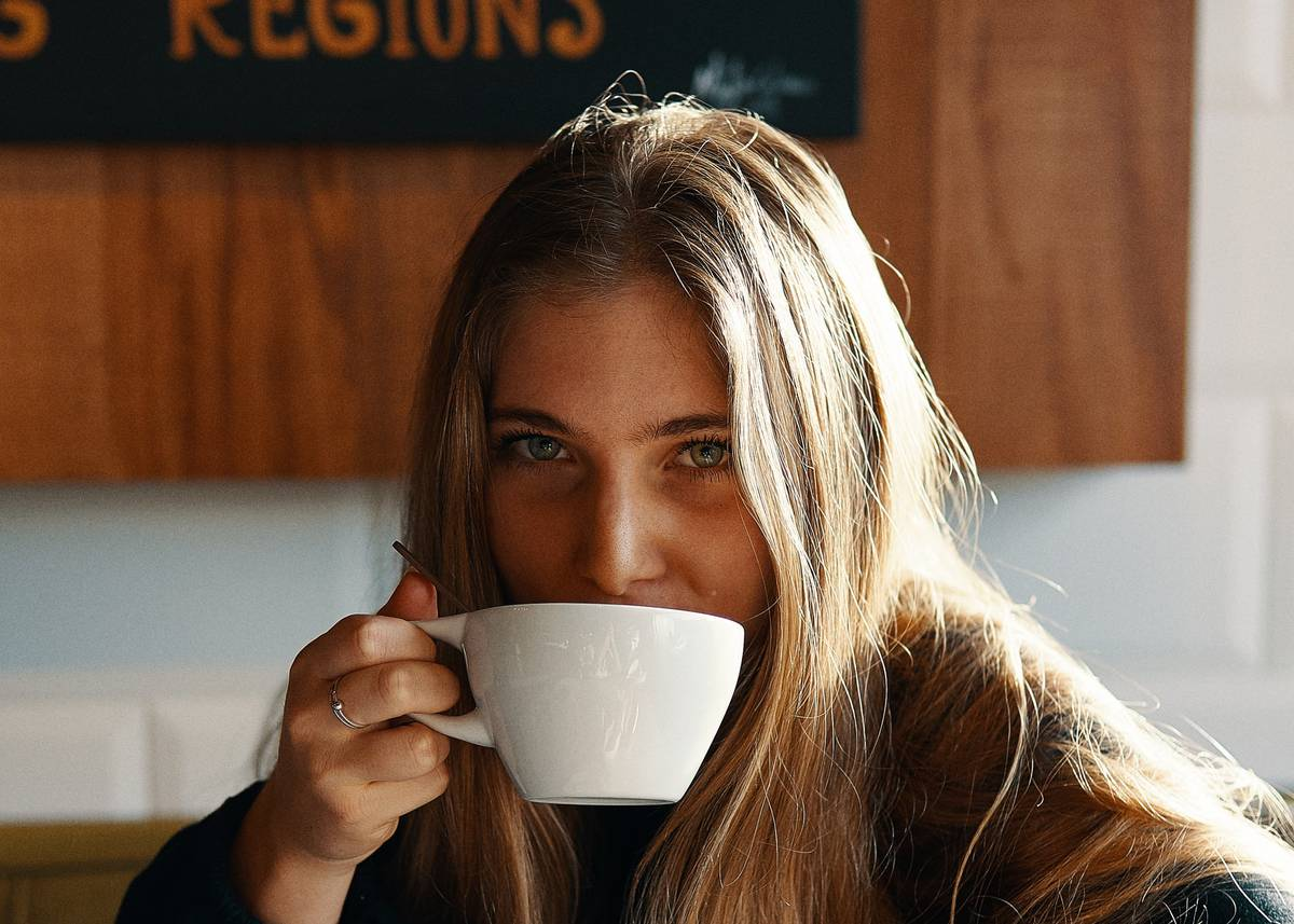 A woman drinks coffee at a cafe.