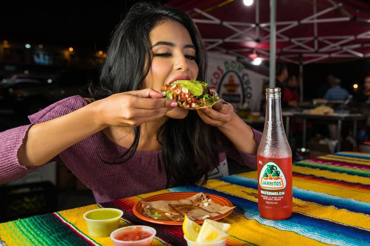 A woman eats tacos at night.