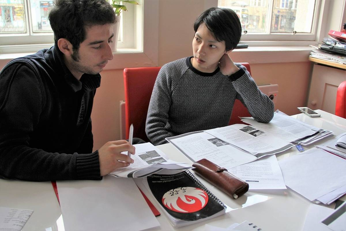 An instructor teaches a second language to a student.