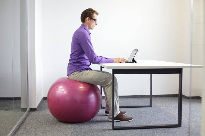 A man works on his laptop while sitting on an exercise ball.