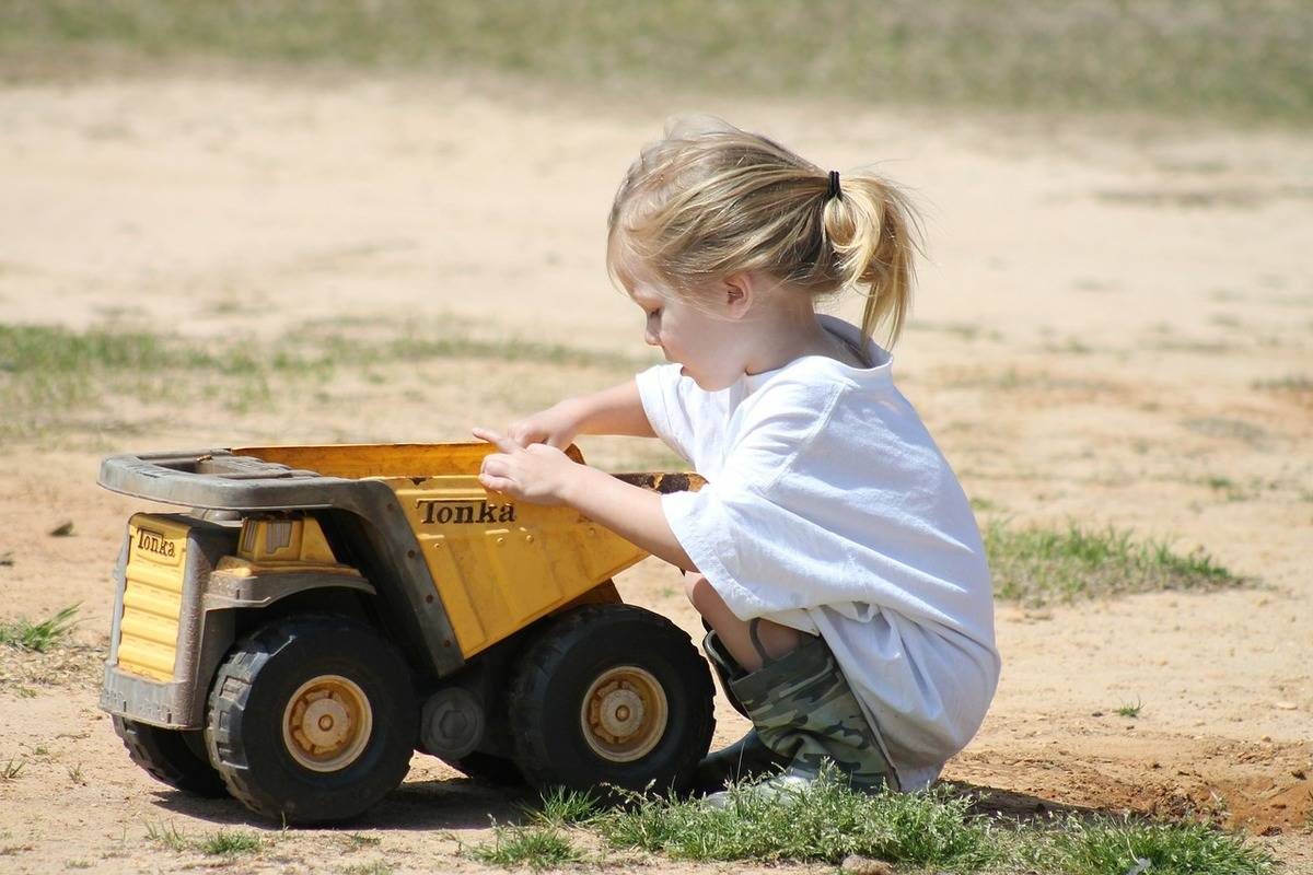 A child plays in dirt with a toy truck.
