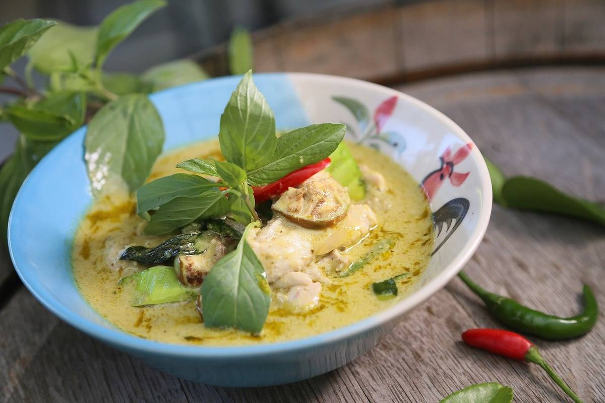 A green curry dish sits on a wooden table.