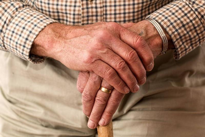 A senior citizen clutches a walking cane.