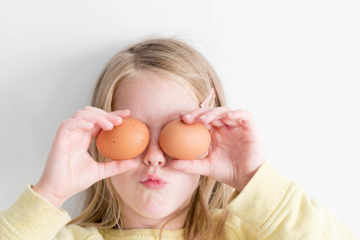 A young girl holds two eggs in front of her eyes.