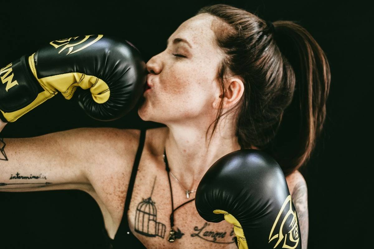 A boxer playfully kisses her boxing glove.