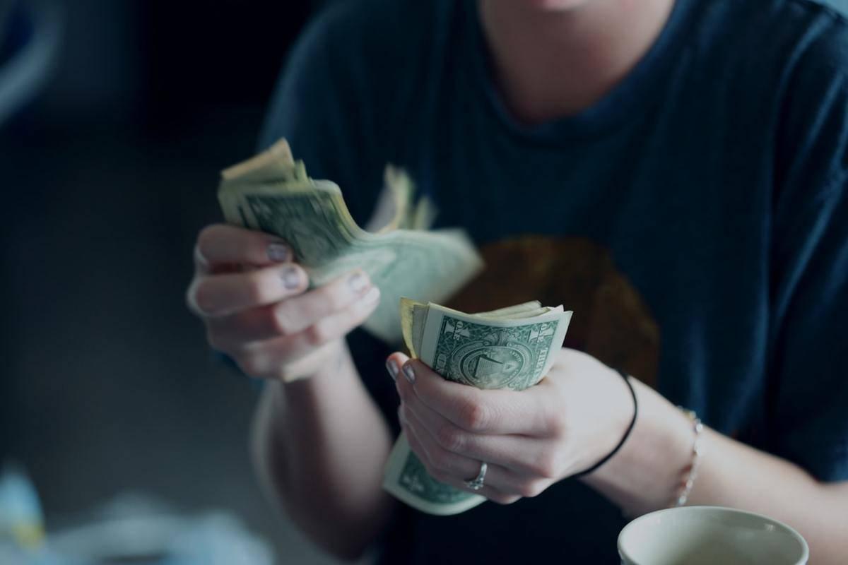A person counts dollar bills.