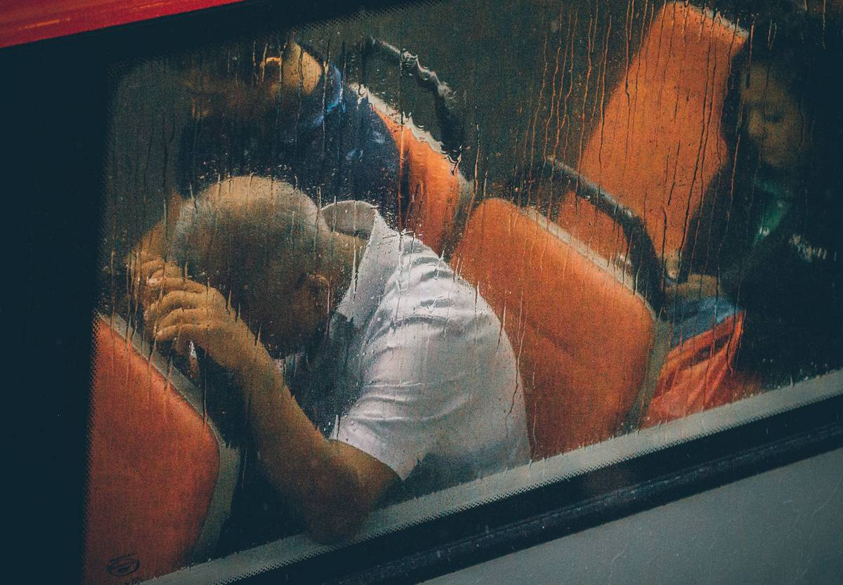 A man on a bus leans his head against the back seat.
