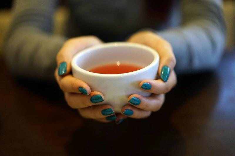 A woman holds a cup of tea.