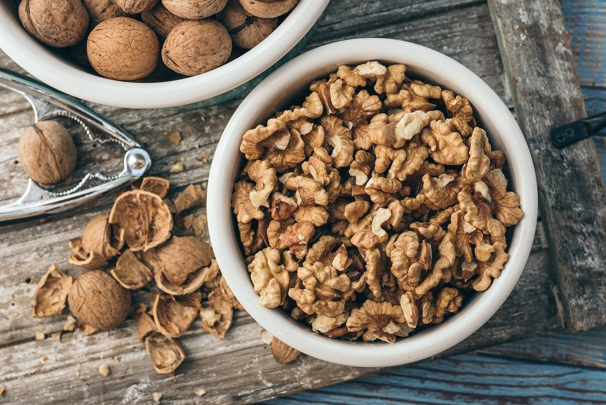 A bowl of walnuts sits on a wooden surface.