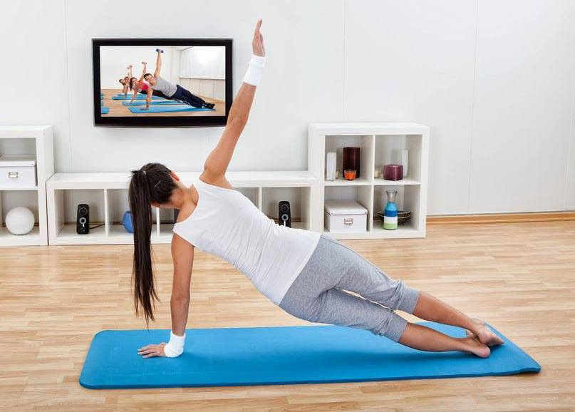 A woman performs yoga while watching a class on her TV.