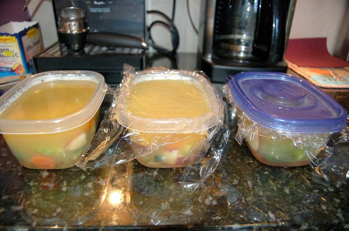 Soup is held in plastic containers covered in plastic wrap.