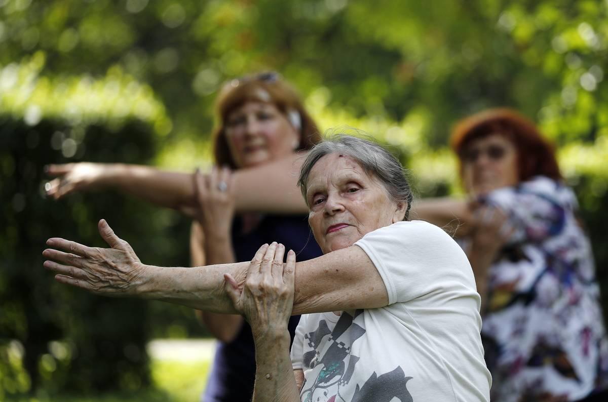 Elderly people practice yoga in a park.