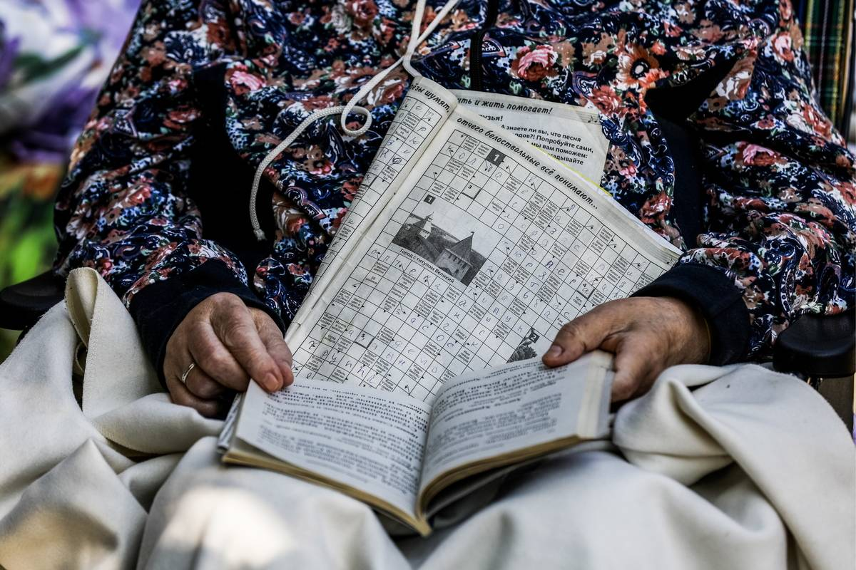 A woman reads a book and works on a crossword puzzle.