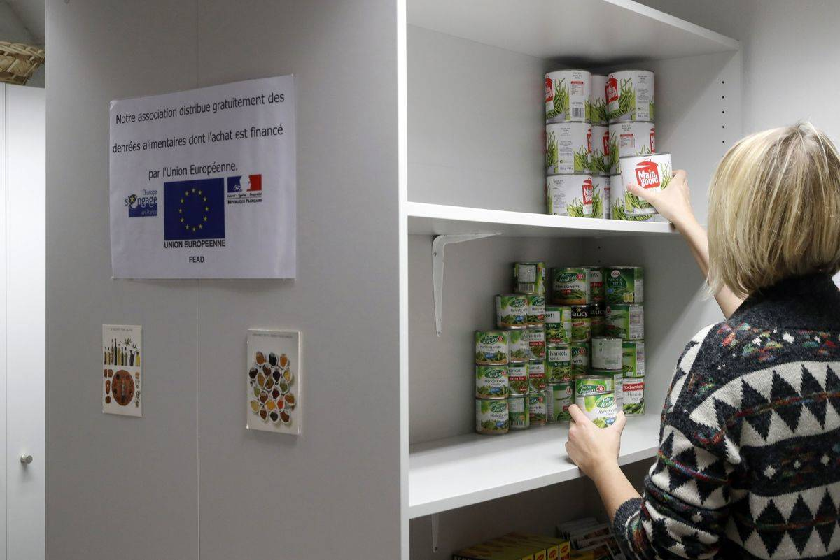 A woman stacks canned food for a French donation center.