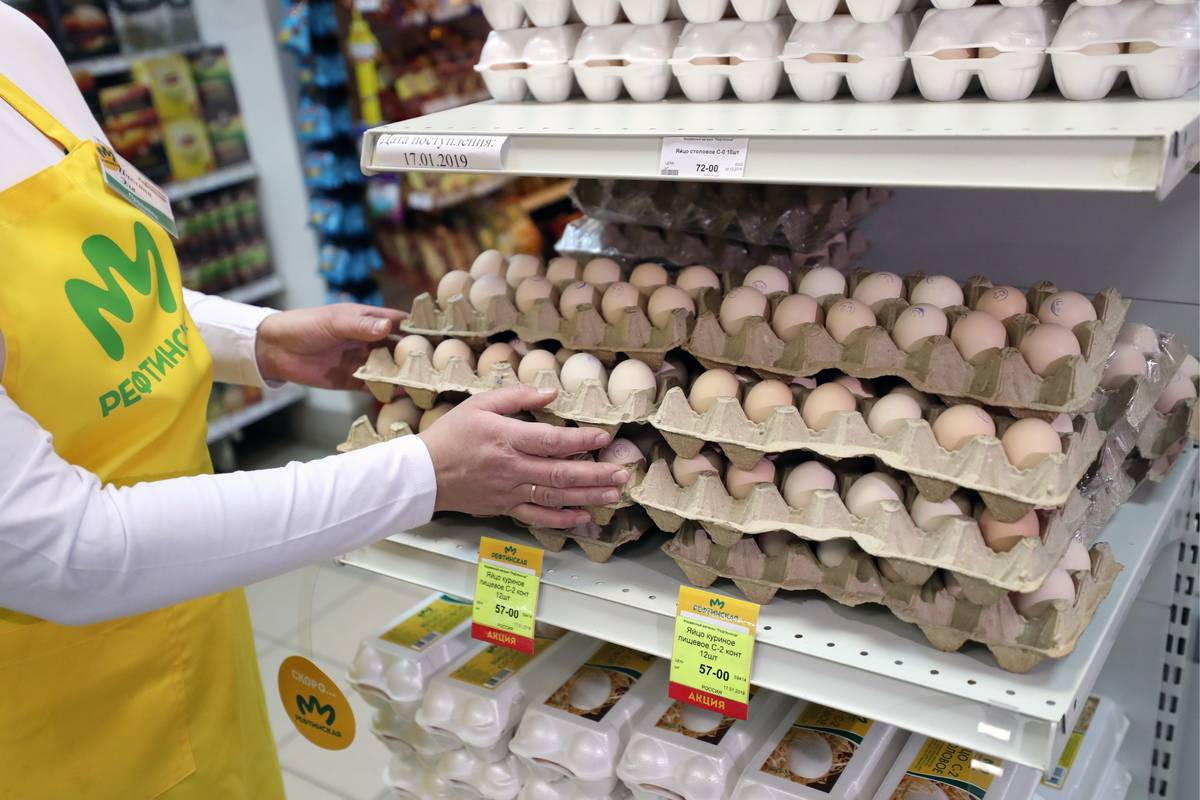 An employee stacks egg cartons at a grocery store.
